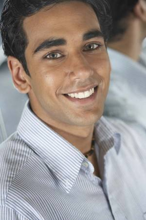 Young man with blue shirt smiling